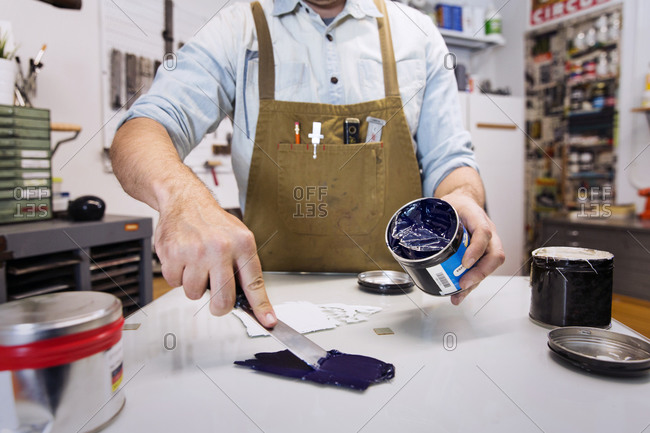 Man mixing inks in a printmaking workshop