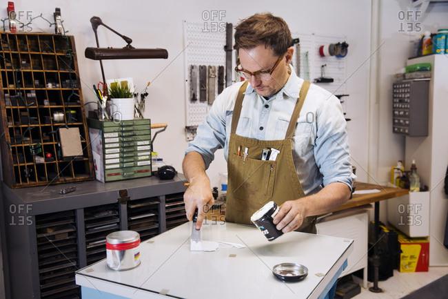 Printmaker mixing inks in a workshop