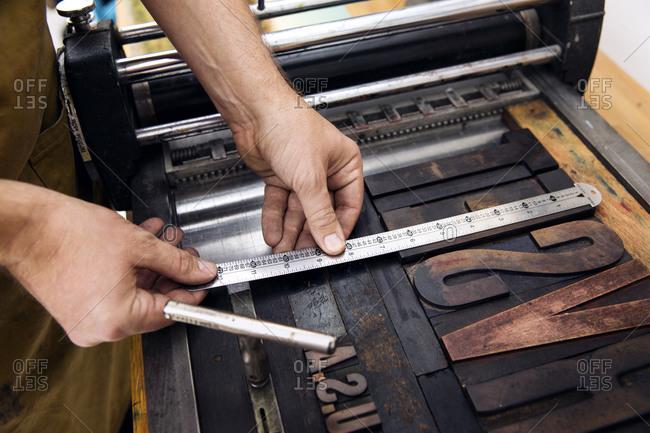 Man measuring type in a letterpress studio