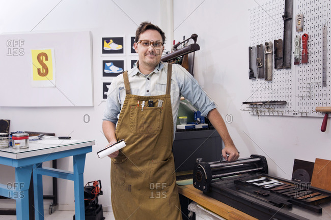 Portrait of a printmaker inking letterpress type