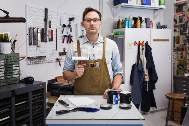 Portrait of a printmaker with an inked roller