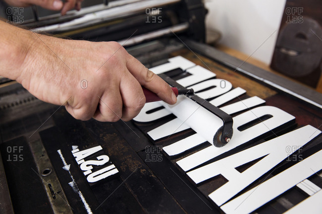 Close up of a printmaker inking letterpress type