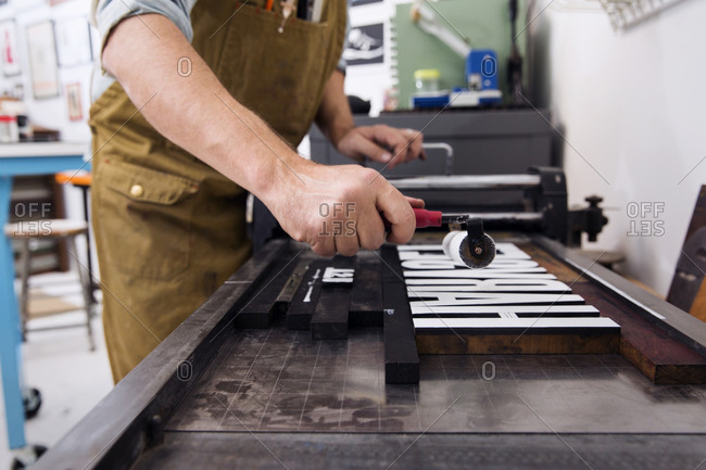 Printmaker inking letterpress type