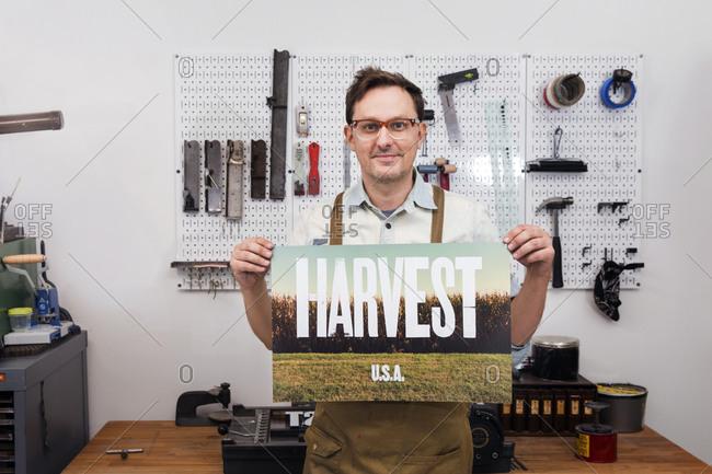Printmaker holding print he just made in studio