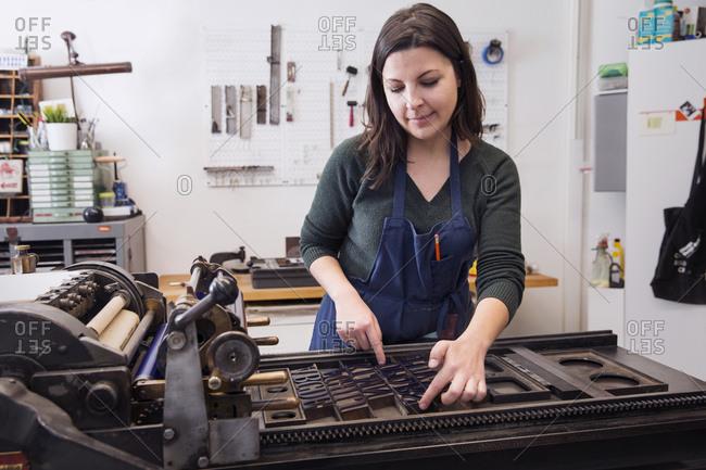 Woman adjusting type on a letterpress printing press