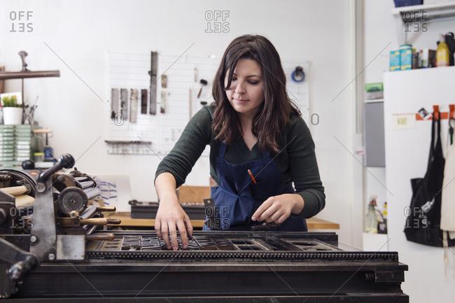 Printmaker adjusting type on a letterpress printing press