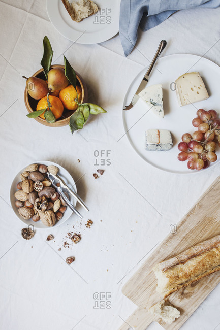 Appetizer table with nuts, cheese, bread and grapes