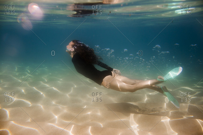Woman in long sleeved swimsuit underwater