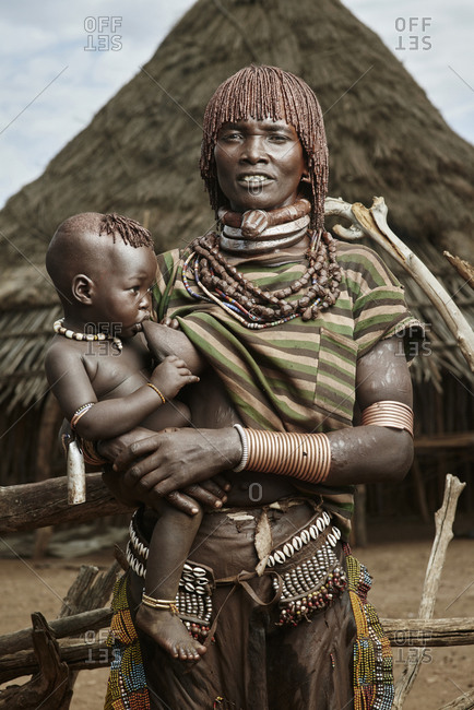 February 13, 2015:  Portrait of Hamar woman with nursing baby in front of peak-roofed hut