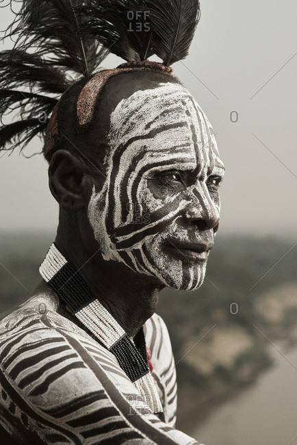 February 14, 2015: Portrait of a Karo tribesman with intricate face and body paint and feathers in his hair