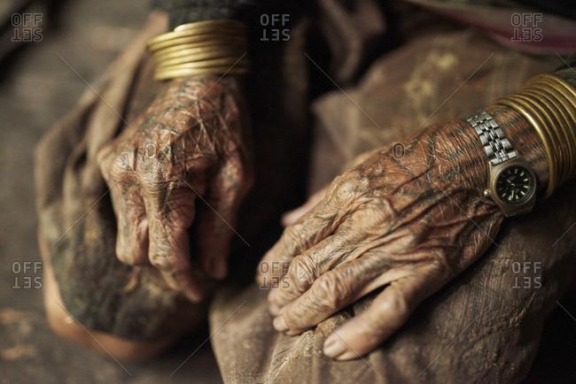 November 15, 2013: Hands of an elderly Mentawai man with a wristwatch and brass bracelets
