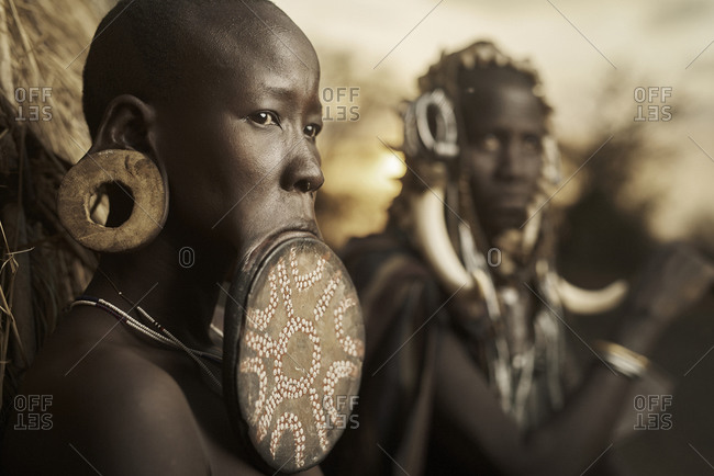 February 20, 2015: Woman with large wooden lip plate and stretched earlobes standing with a fellow Mursi tribe member