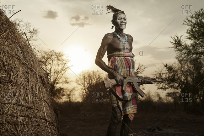 February 20, 2015: Mursi tribesman standing with rifle outside a grass hut