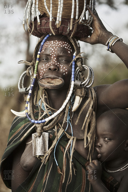 February 19, 2015: Mursi woman with lip plate and basket on her head carries her nursing baby on her hip
