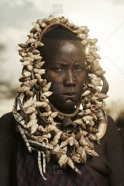 February 20, 2015: Portrait of Mursi woman wearing a headdress adorned with seashells and metal beads