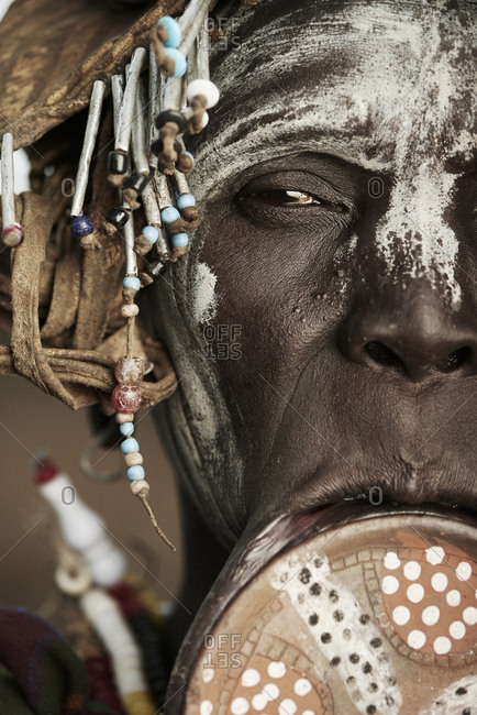 February 19, 2015: Close-up portrait of a member of the Mursi tribe with lip plate and white face paint