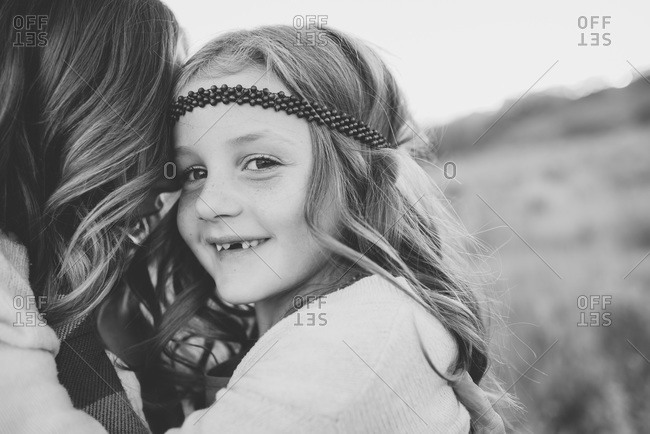 Close up of daughter looking over mother's shoulder in black and white