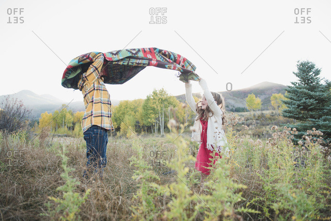 Brother and sister throwing blanket in the air