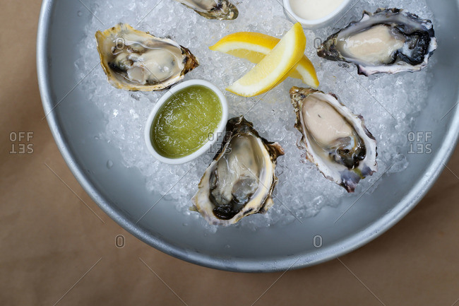 Oysters in a bowl filled with ice and lemons