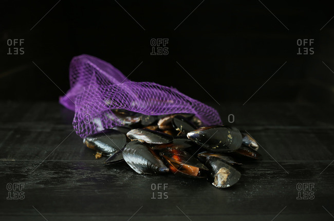 Mussels spilling out of a purple net