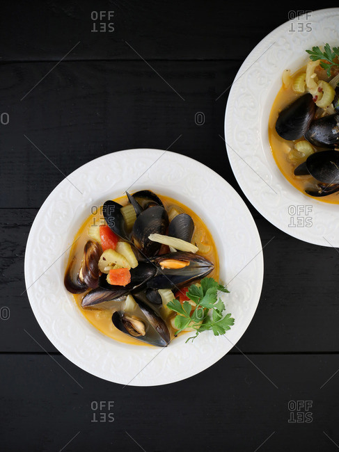 Bowls of mussel soup with celery and tomatoes