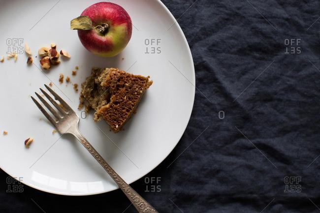 Half eaten slice of apple cake and an apple