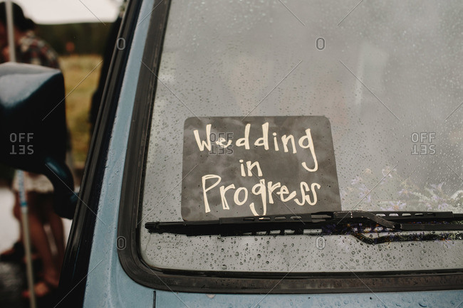 Wedding in progress sign on vehicle windshield