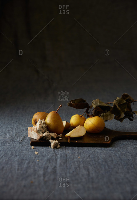 Yellow apples on a branch with cheese and pears on a wooden cutting board