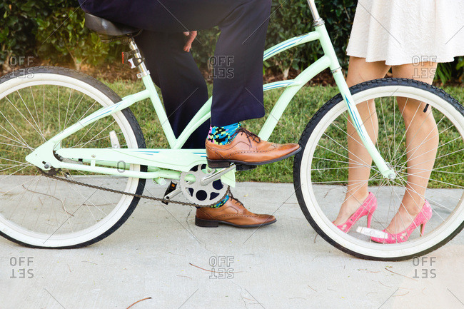 Low section of stylish couple with bike