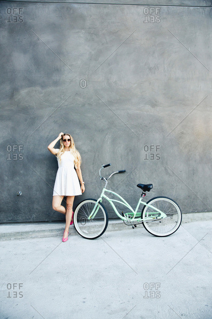 Hip woman leaning on wall by bike