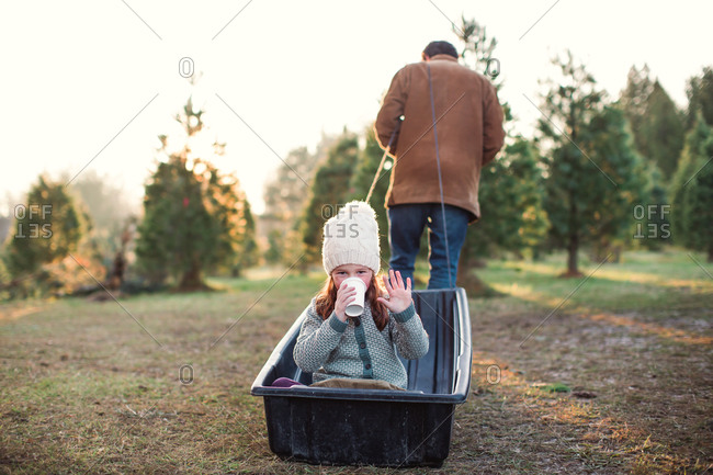 Little girl drinking hot cocoa and waving while being pulled in a sled