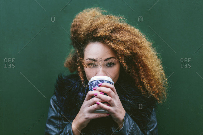 Portrait of woman drinking coffee to go in front of a green wall