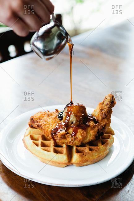 Syrup being poured over fried chicken and waffles