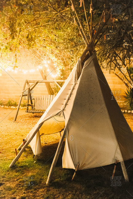 Tepee lit by string lights in a backyard