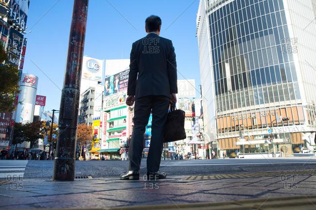 Tokyo, Japan - November 20, 2015: Low angle view of businessman with briefcase at street corner at Shibuya Crossing, Tokyo, Japan