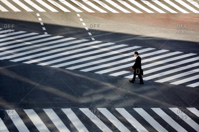 Elevated view of a businessman walking at Shibuya Crossing, Tokyo, Japan