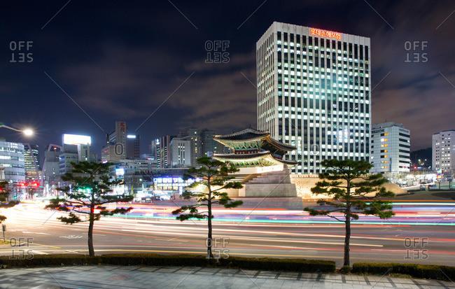 Seoul, South Korea - December 4, 2015: Blurred traffic driving past Sungnyemunn gate in Seoul, South Korea, at night