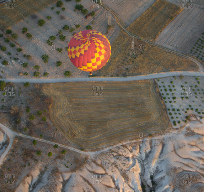 Overhead view of hot air balloon flying over rural farming landscape