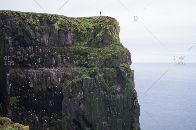 Man standing on cliff at Latrabjarg, Iceland