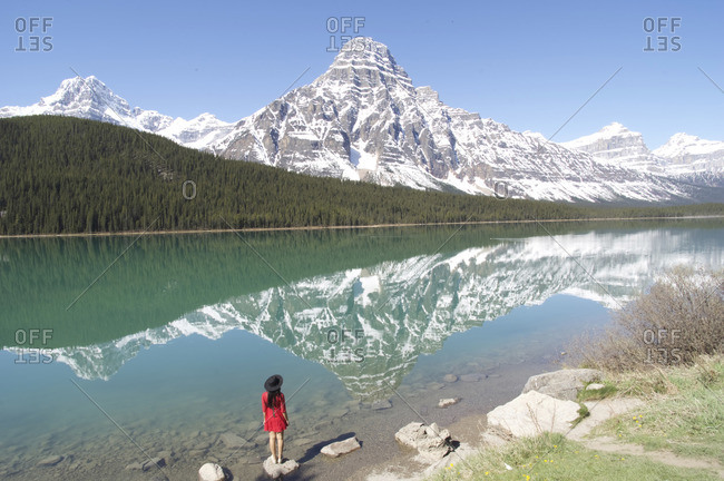 Woman standing at edge of Waterfowl Lake below Mount Chephren in Banff National Park