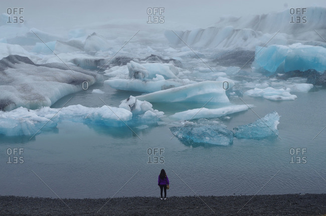 Back view of woman viewing glaciers from beach in misty landscape