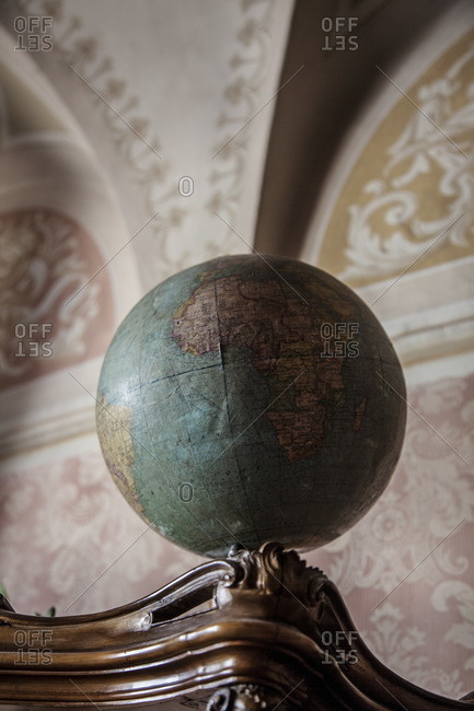 Lugano, Switzerland - September 25, 2015: Antique globe of Earth on top of an old cabinet