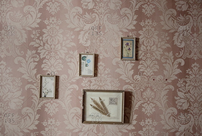 Lugano, Switzerland - September 25, 2015: Pictures hanging on a wallpapered wall of an old house