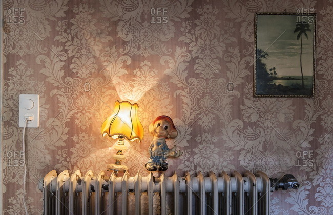 Lugano, Switzerland - September 25, 2015: Lamp and dwarf figure on a radiator of an old house