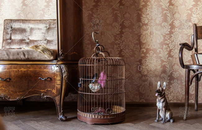 Lugano, Switzerland - September 25, 2015: Wooden birdcage and a dog statue in an old house