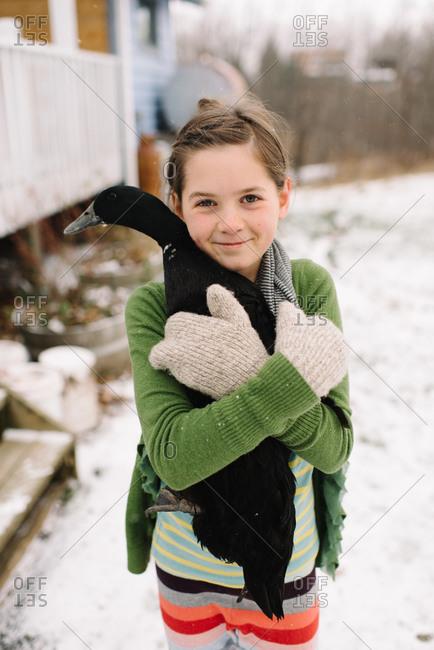 Little girl holding a black duck