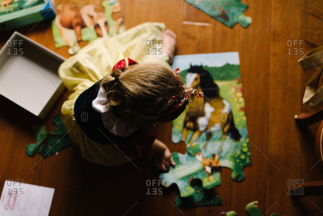 Little girl putting together a horse puzzle