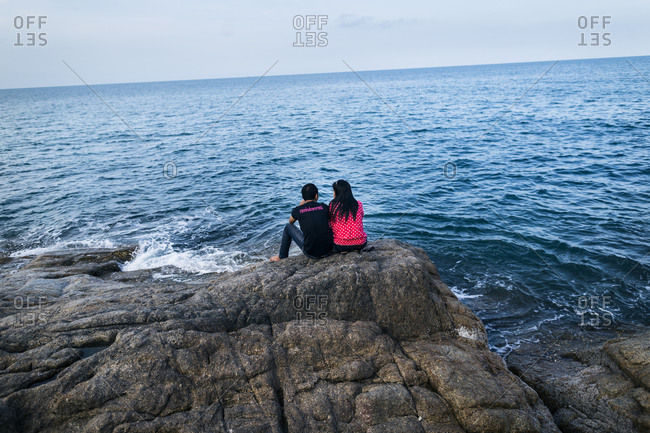Couple sitting on rock coast