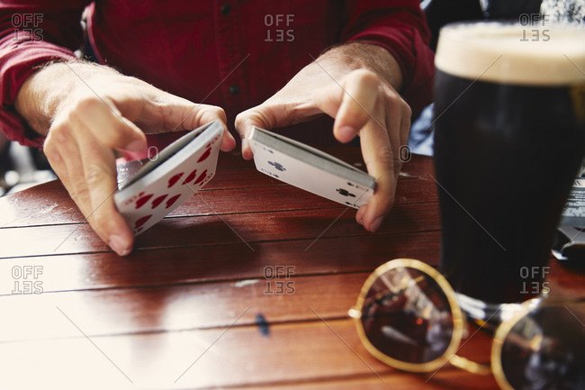 Man shuffling cards with a beer