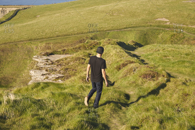 Man walking in coastal hills